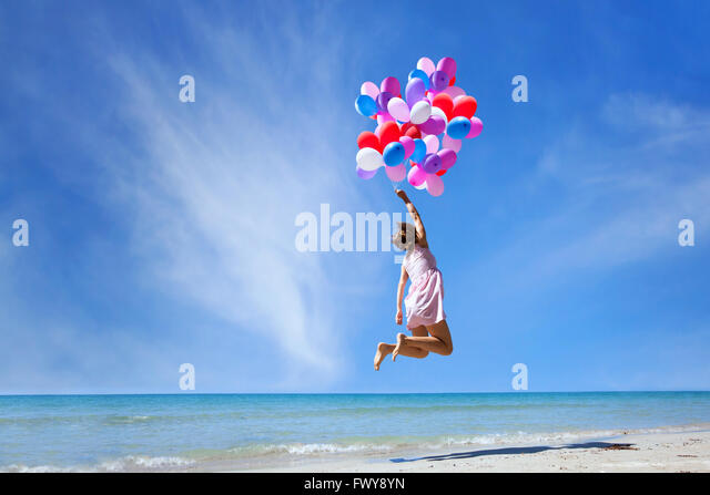 dream concept, girl flying on multicolored balloons in blue sky, imagination and creativity - Stock Image