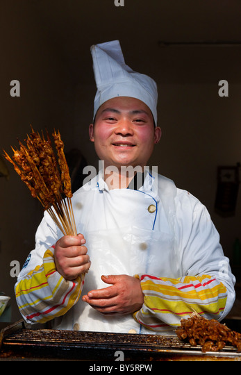 Street kebab fast food seller in the ancient town of Huanglongxi near Chengdu in the Sichuan Province of China. - Stock Image