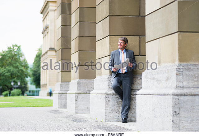 Mature businessman leaning against building reading newspaper - Stock Image