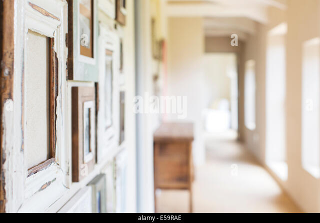 Decorative wall frames in rustic hallway - Stock Image