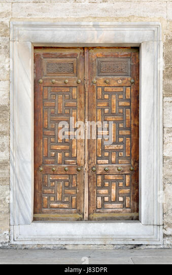 Wooden aged engraved door and exterior stone wall, Sultan Ahmet Mosque, Istanbul, Turkey - Stock Image