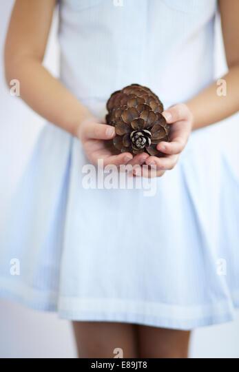 Girl holding large pinecone - Stock-Bilder