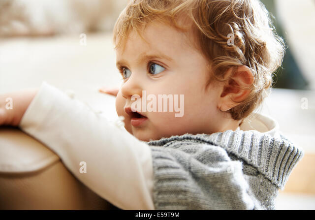 Baby girl clinging to edge of sofa - Stock Image