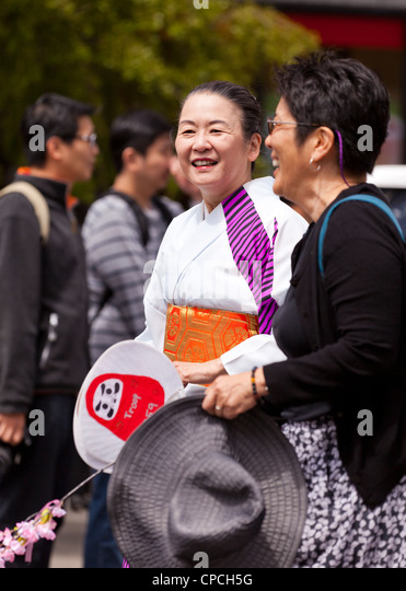 A middle aged Japanese woman wearing a kimono at a festival - Stock Image
