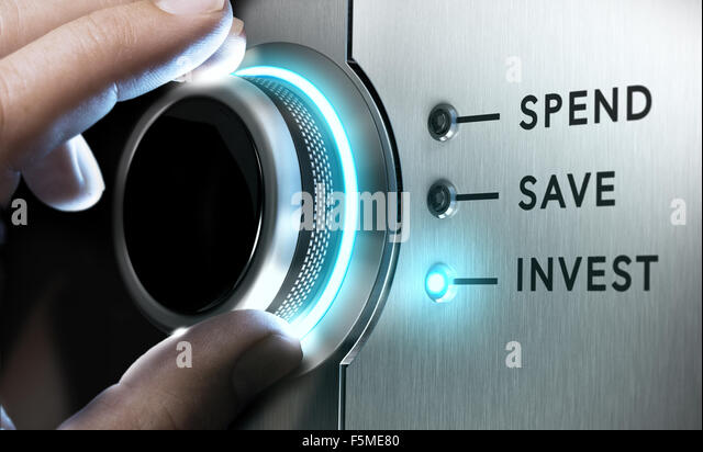Man hand turning a knob in the invest position,  Concept image for illustration of making an investment versus saving - Stock Image