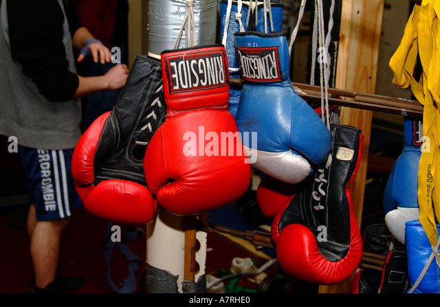 Boxing gloves and ring in a beat up inner city training center - Stock Image