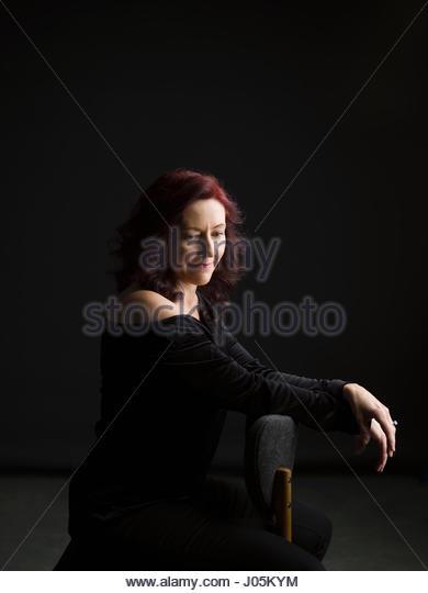 Portrait pensive woman looking down against black background - Stock Image