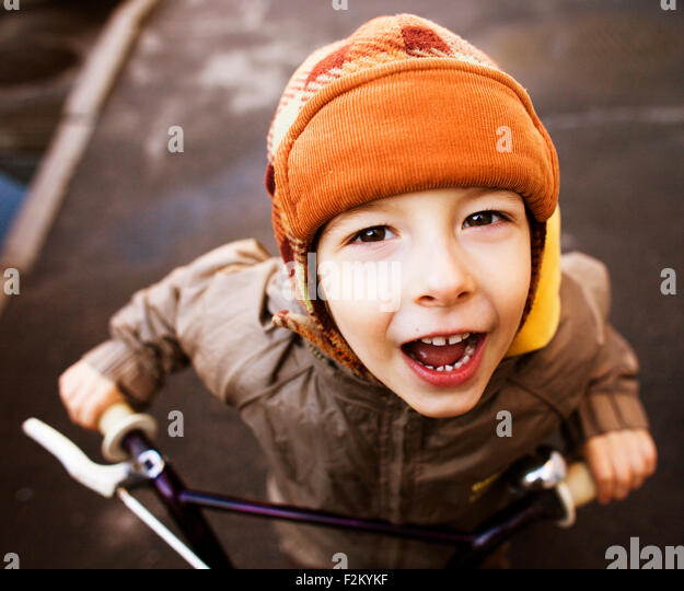 little cute boy on bicycle smiling close up in hat - Stock Image