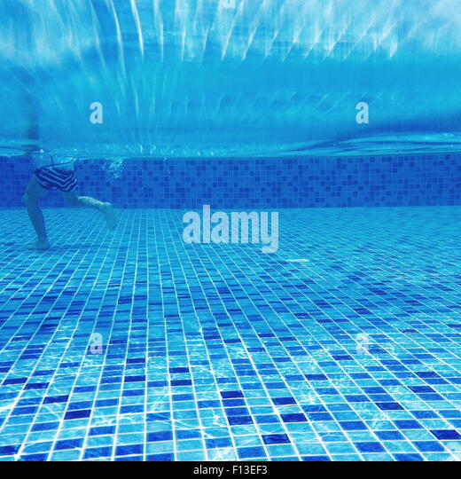 Underwater view of a boy walking in a swimming pool - Stock Image