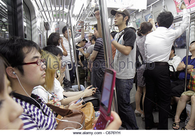 Japan Tokyo Shinagawa Station JR Yamanote Line commuters riders Asian man standing sitting mobile cell phone - Stock Image
