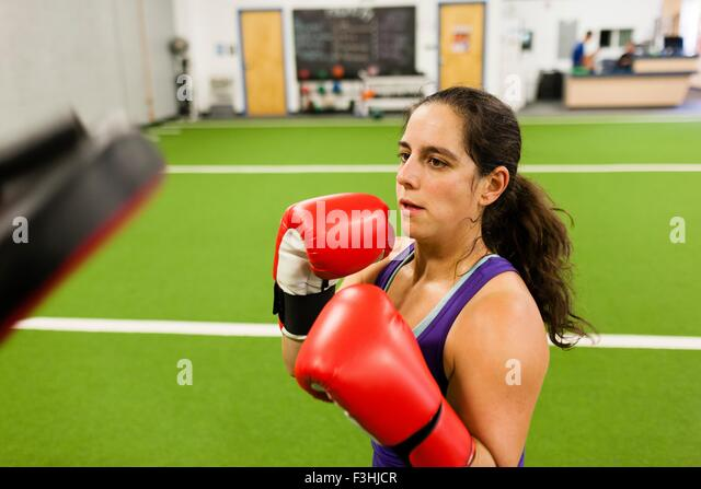 Mid adult woman wearing boxing gloves, working out in gym - Stock Image