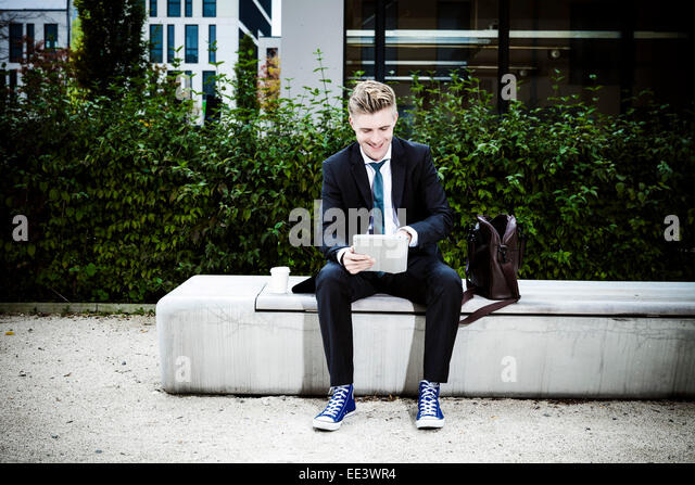 Young businessman using digital tablet outdoors, Munich, Bavaria, Germany - Stock-Bilder