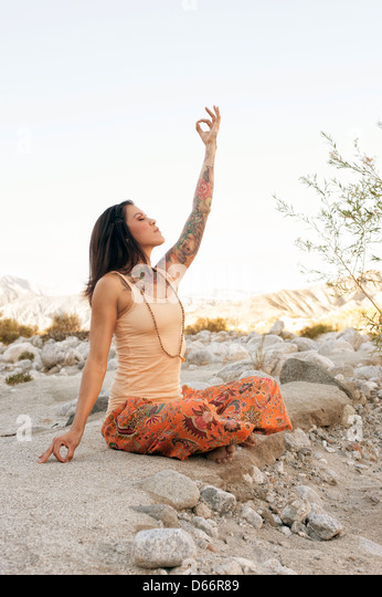 Yoga Woman outdoors touching earth and sky. - Stock Image