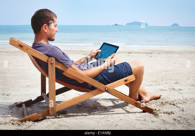 business man working with tablet on the beach - Stock Image
