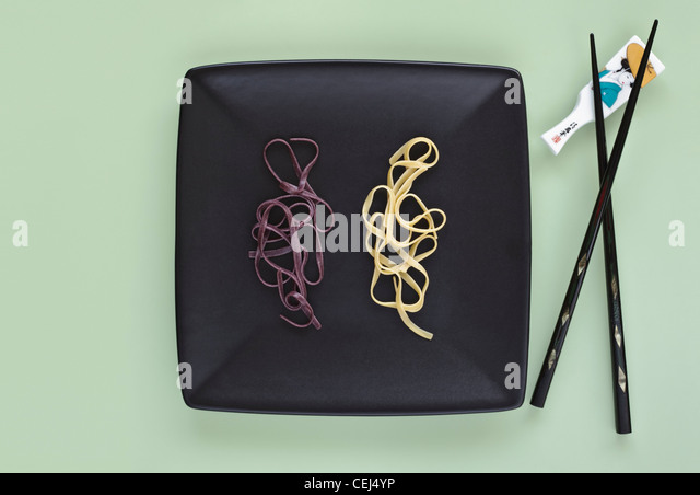Black and White Rice Noodles on Plate with Chopsticks - Stock Image