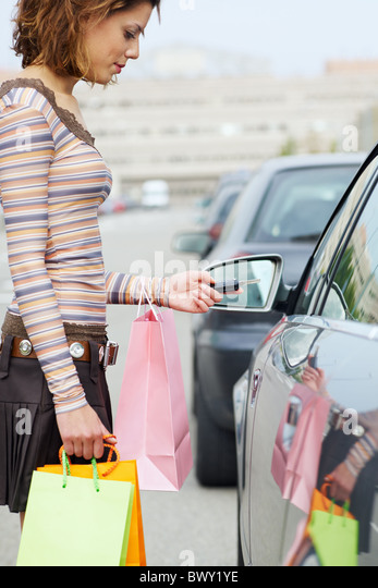 woman with shopping bags holding car keys - Stock Image