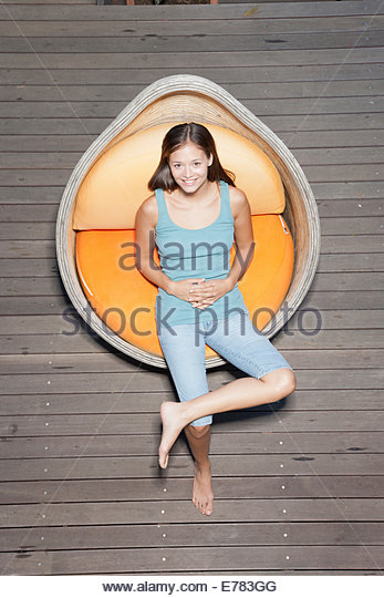 A young woman sitting on a deck - Stock Image