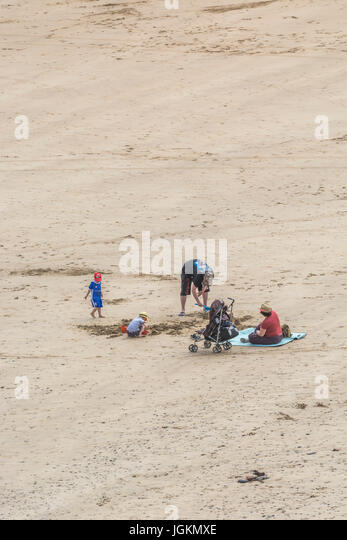 Family on a beach at Newquay, Cornwall. - Stock Image