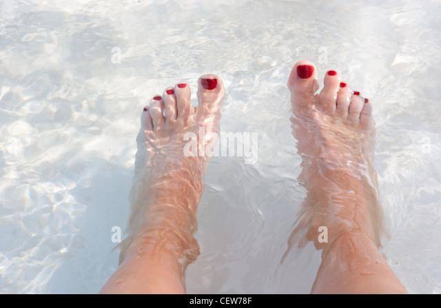 Feet in water with red toenail polish - Stock-Bilder