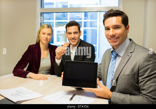 Smiling businessman showing a new project on tablet at young couple, new property owners - Stock Image