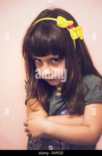 Angry child girl portrait at home in soft tones - Stock Image