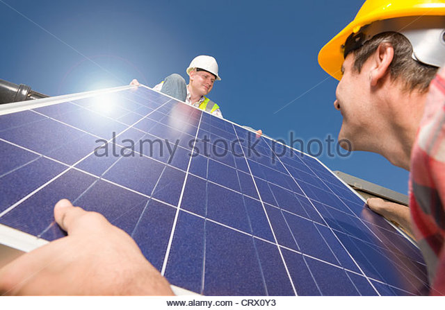 Engineers lifting solar panel onto roof - Stock Image