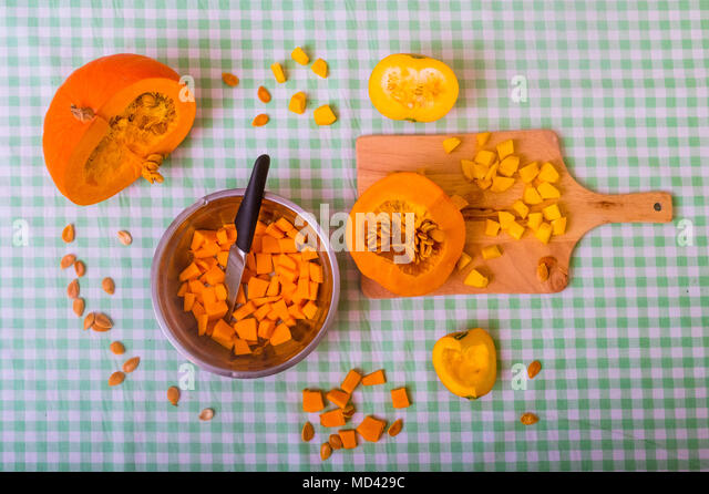 Pumpkin cut into pieces on chopping board with bowl full of cubed pumpkin, overhead view - Stock Image