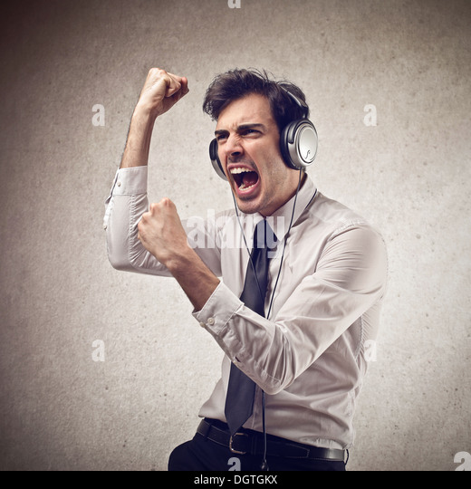 Young office worker dancing while is listening to the music with headphones - Stock Image