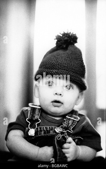 Photograph of bobble hat young child wide eyed alert baby funny - Stock-Bilder