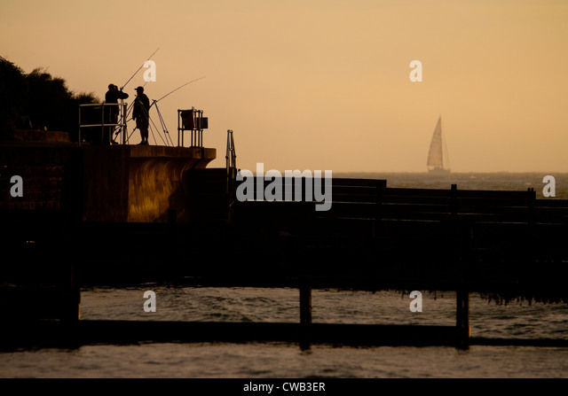 Angling, Fishing, Fishermen, Seawall, groynes, yacht, mist, Colwell Bay, Isle of Wight, England, UK, - Stock Image