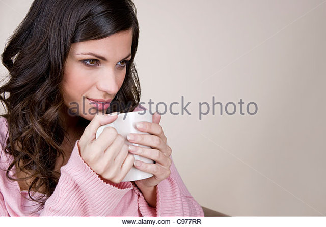 A young woman drinking a cup of hot chocolate - Stock Image