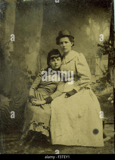 Mother and daughter in dresses during a photo sitting that produced a tin-type photograph during the late 1800s - Stock-Bilder