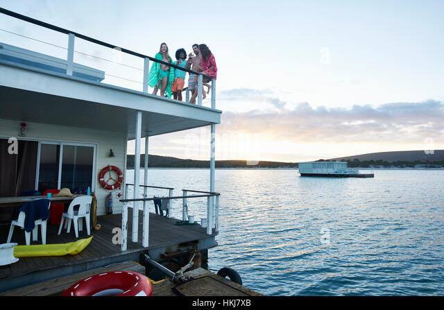 Young adult friends hanging out on deck of summer houseboat on ocean - Stock-Bilder