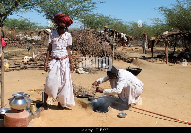 Men cooking food using earthen oven in Kutch, Gujarat, India - Stock Image