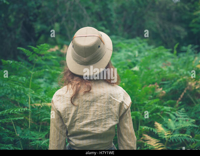 A young woman wearing a safari hat is exploring a forest with lots of green ferns - Stock Image