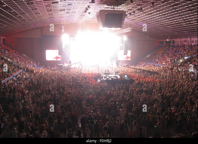 Numerous of cheering crowd in a concert hall during a rock concert - Stock Image