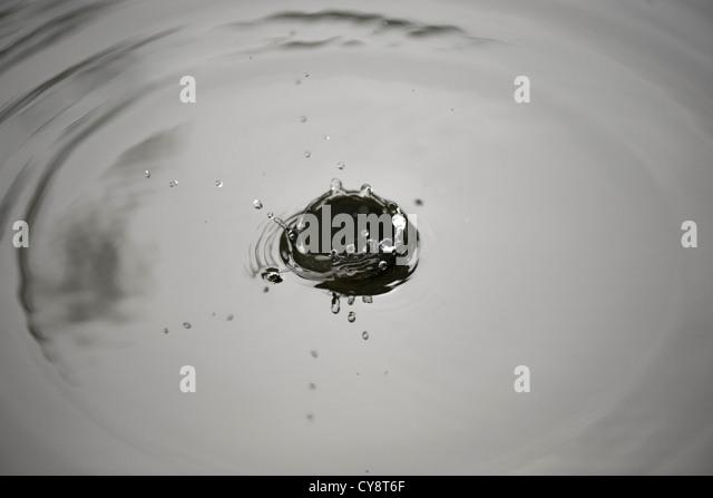 Drop splashing on surface of water - Stock Image