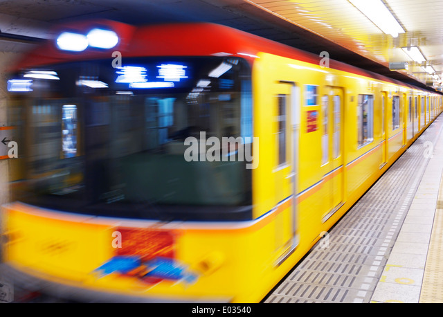 Tokyo Metro yellow subway train blurred from motion arriving to a platform. Tokyo, Japan. - Stock Image