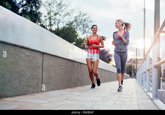 Beautiful scenery of two female joggers pursuing their activity outdoors in the city in dusk - Stock Image