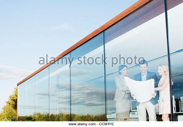 Architects with blueprint in office window - Stock Image