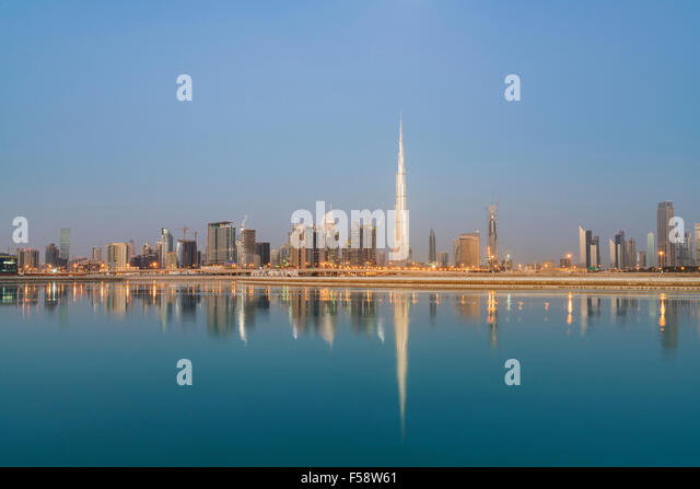 Skyline of skyscrapers and Burj Khalifa tower before sunrise in Dubai United Arab Emirates - Stock-Bilder
