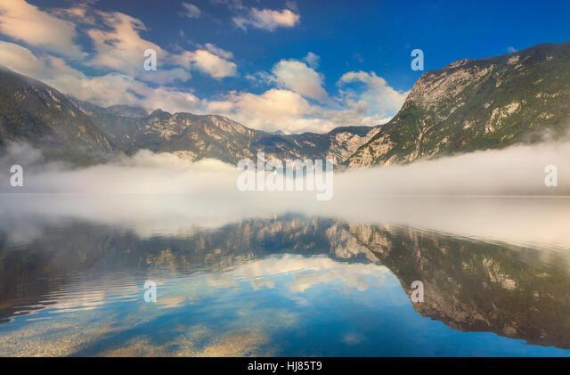 Foggy summer morning on the Bohinj lake in Triglav national park Slovenia, Alps, Europe. - Stock Image