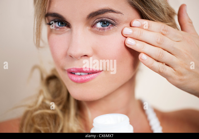 A young blonde woman applying moisturiser to her face, close up - Stock Image