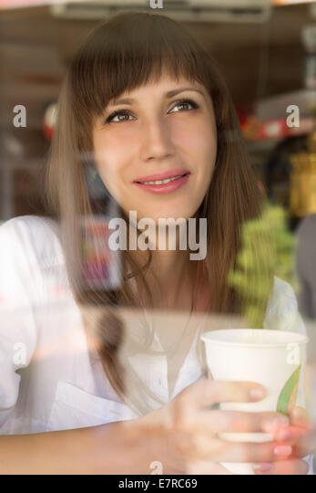 Smiling young woman at the cafe with cup of coffee or tea - Stock-Bilder