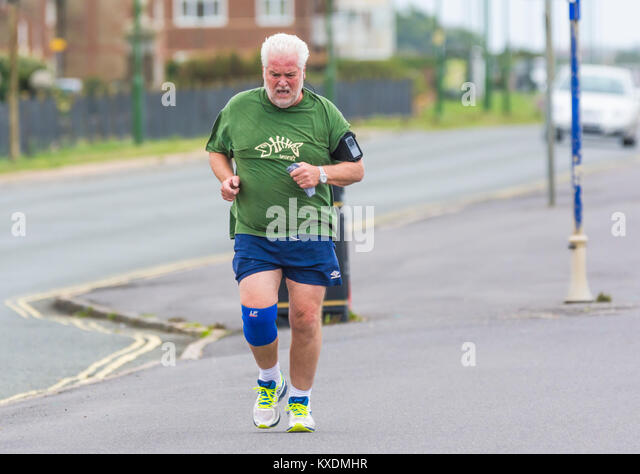 Middle aged man wearing a fitness tracker having a morning jog. - Stock Image