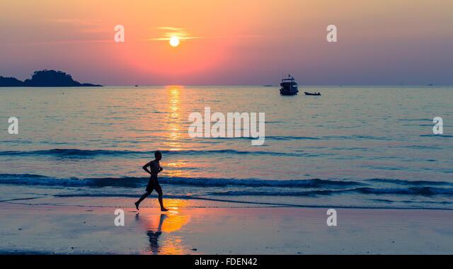 Silhouette of men running on coast line during amazing sunset. - Stock-Bilder
