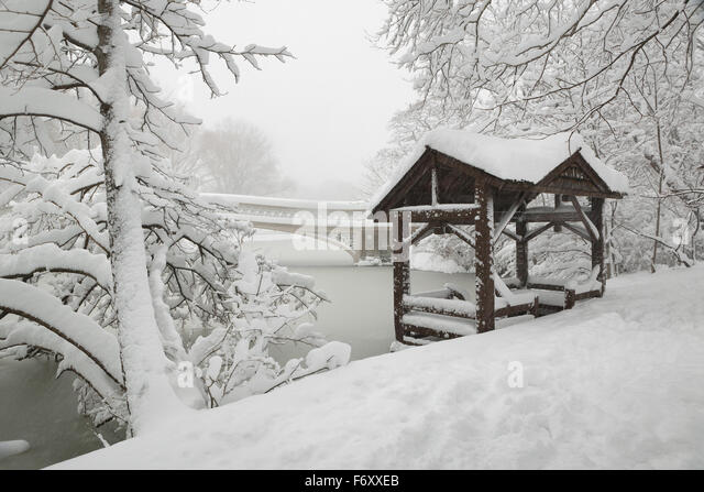 Central Park peaceful winter scene after heavy snowfall. The Bow Bridge and a wooden gazebo are covered in snow. - Stock Image