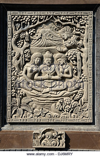 Relief carving panel on wall of Balinese Hindu temple depicting trinity of the three deities Brahma Shiva and Vishnui - Stock Image