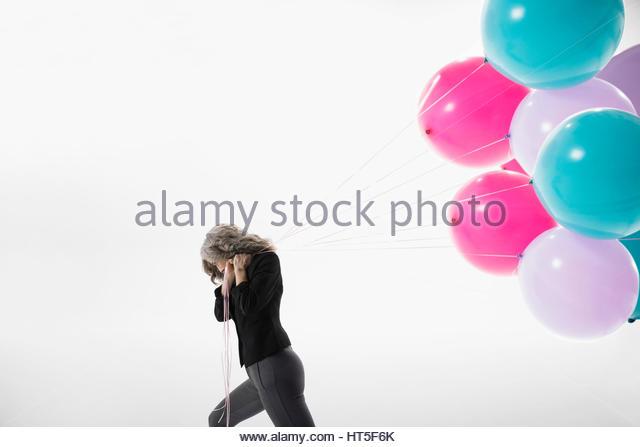 Woman pulling bunch of vibrant balloons against white background - Stock-Bilder