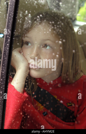 Young  sad girl looking bored gazes  through a rain covered car window - Stock Image